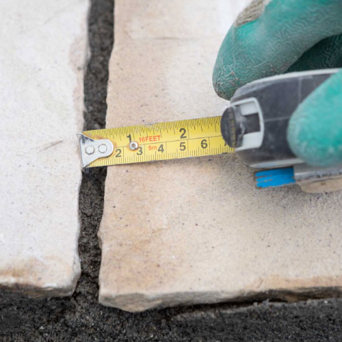 Checking the spacing of the gap between patio slabs